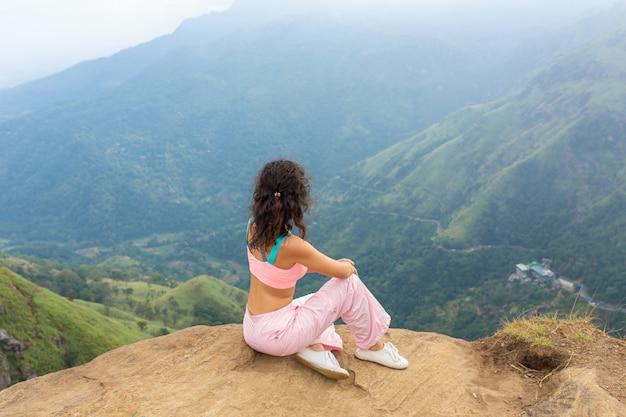 La ragazza gode di una vista sulle montagne, mentre in piedi su una scogliera