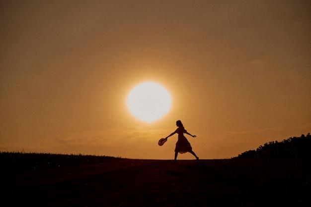 La ragazza gode e si diverte al tramonto all'aperto.
