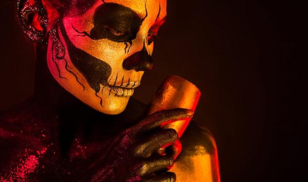 La ragazza graziosa con trucco di scheletro tiene il vetro