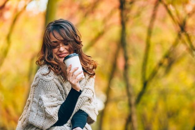 La ragazza graziosa con una tazza della bevanda calda sorride nella foresta in autunno.