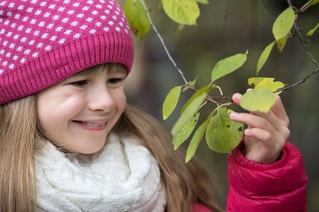 La ragazza graziosa del bambino che indossa l'inverno caldo copre la tenuta del ramo di albero con le foglie verdi nella stagione fredda all'aperto.