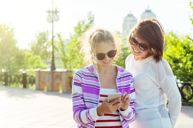 La ragazza graziosa e la sua bella madre usano gli smartphone