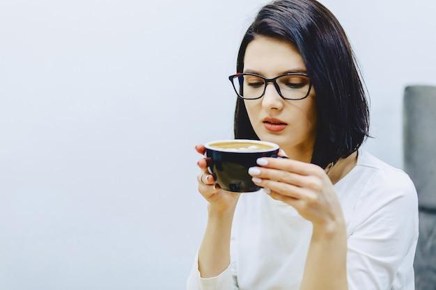 La ragazza graziosa in caffè beve il caffè