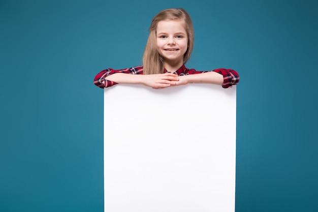 La ragazza graziosa in camicia con capelli lunghi tiene il cartello in bianco bianco
