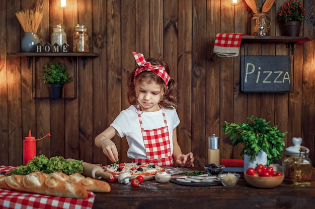 La ragazza graziosa in grembiule a quadretti spruzza la pizza con la pizza di verdi