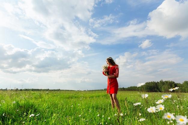 La ragazza graziosa in vestiti ucraini tradizionali sta nel verde