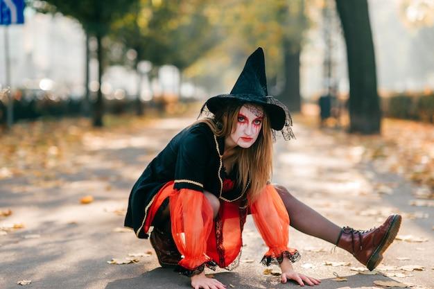 La ragazza graziosa in vestito dalla strega con il grande cappello nero propone all'esterno.