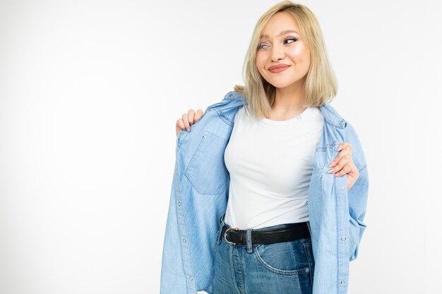 La ragazza graziosa pazza con capelli biondi in jeans alla moda copre la posa su un fondo bianco con lo spazio della copia