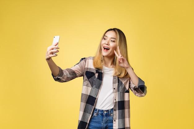 La ragazza graziosa prende un autoritratto con il suo smartphone. selfie ragazza asiatica