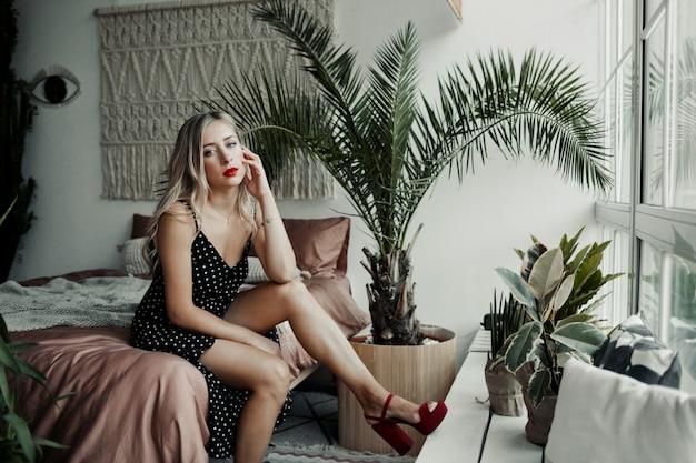 La ragazza graziosa si siede su un letto in una stanza