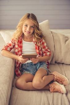 La ragazza graziosa sta usando una compressa digitale