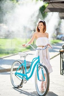 La ragazza graziosa tiene la bicicletta blu dell'annata in estate