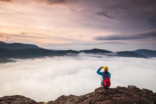 La ragazza guarda al mare di nebbia sull'alta montagna.