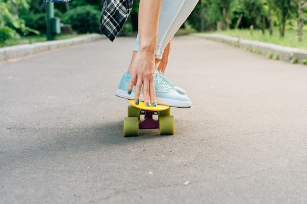 La ragazza guida su uno skateboard sull'asfalto e tiene l'equilibrio