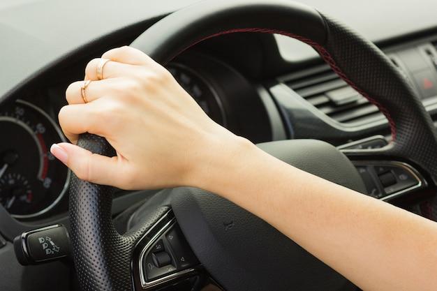 La ragazza guida un'auto, tiene il volante con una mano