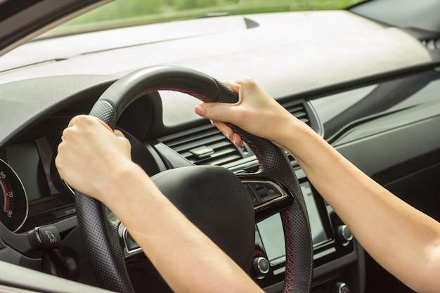 La ragazza guida un'auto, tiene il volante entrambe le mani