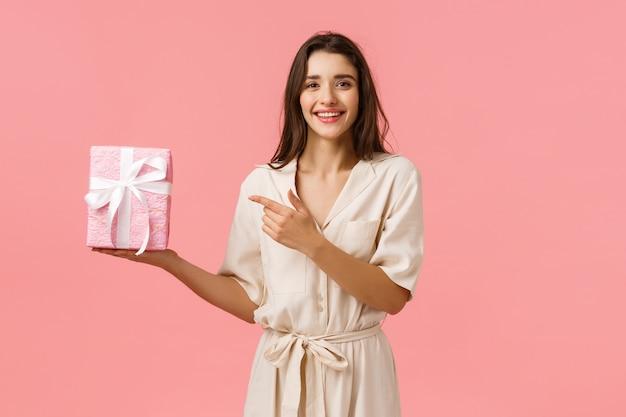 La ragazza ha preparato un regalo romantico per l'anniversario. giovane donna graziosa allegra in contenitore di regalo sveglio della tenuta del vestito e dito puntare attualmente con il sorriso felice e felice, parete rosa stante