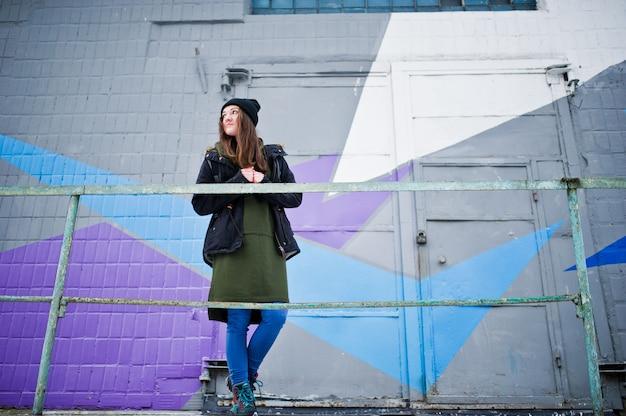 La ragazza ha proposto contro la parete colorata nel giorno freddo.