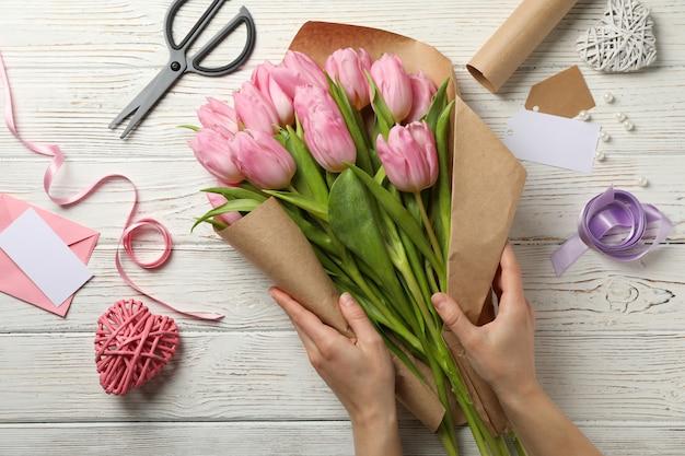 La ragazza imballa i tulipani in carta del mestiere sulla vista di legno e superiore