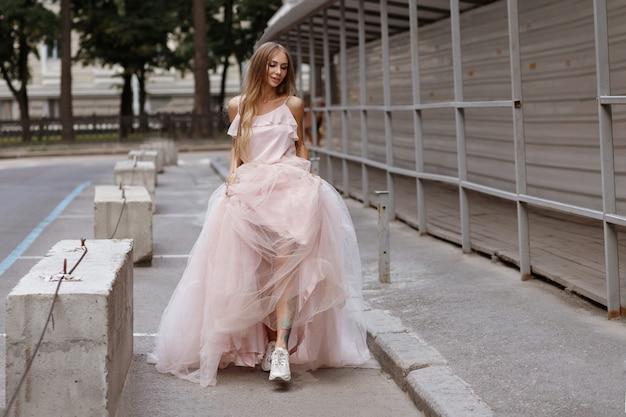La ragazza in abito da sposa lungo e scarpe da ginnastica cammina per la città in estate