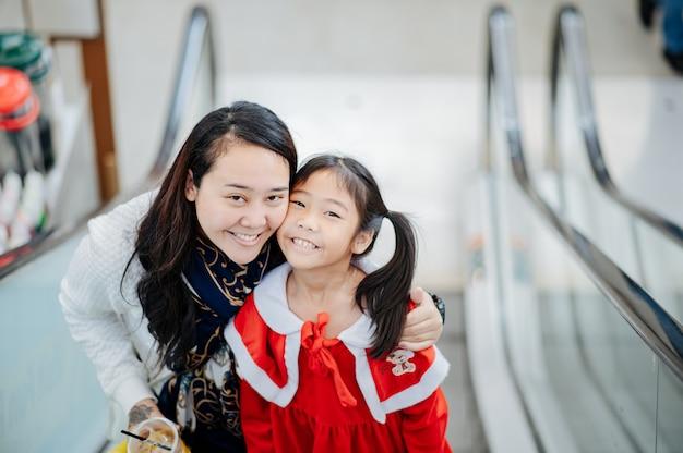 La ragazza in abito sandy sorride, ride, si diverte. con sua madre