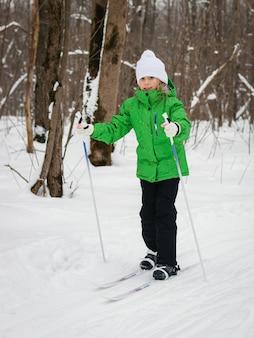 La ragazza in abito verde cammina lentamente attraverso il bosco con gli sci