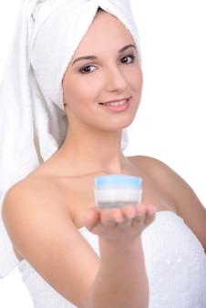 La ragazza in asciugamani tiene a portata di mano una crema.