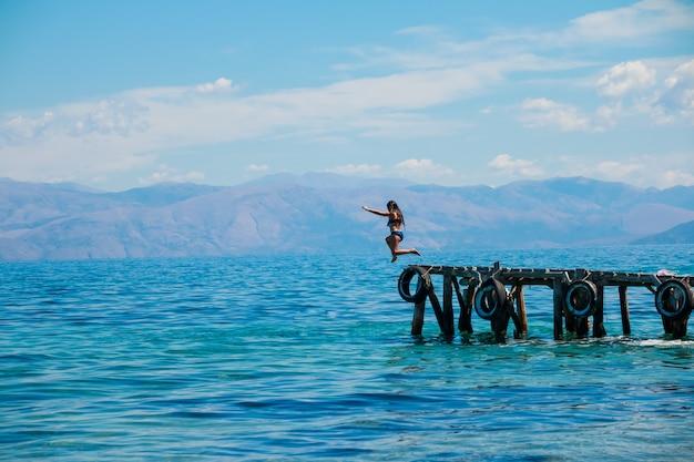 La ragazza in buona salute sportiva sta saltando giù dal pilastro nel sea.jumping dal pilastro nell'acqua.