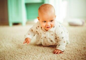 La ragazza in camicia spottata si siede su un tappeto morbido