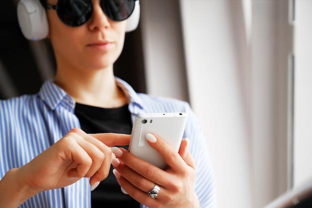 La ragazza in cuffia ascolta la musica, guardando il telefono cellulare, mentre in aeroporto, ufficio.