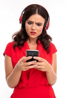La ragazza in cuffie esamina incredulo il telefono