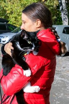 La ragazza in giacca rossa sta tenendo il grande gatto in bianco e nero con l'imbracatura.