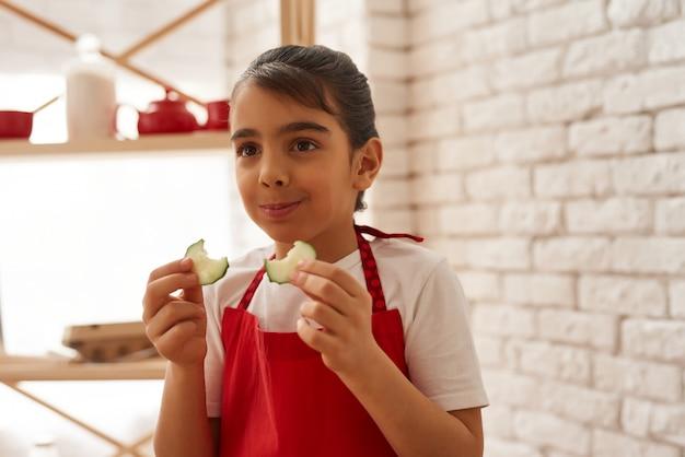 La ragazza in grembiule rosso sta tenendo le fette del cetriolo.