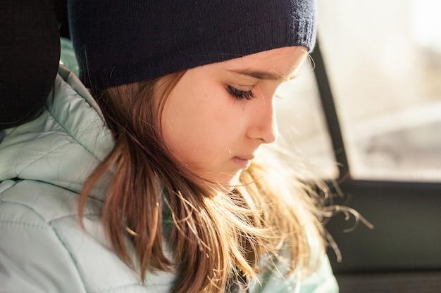 La ragazza in macchina in attesa di un viaggio o di genitori che usano il telefono o i gadget