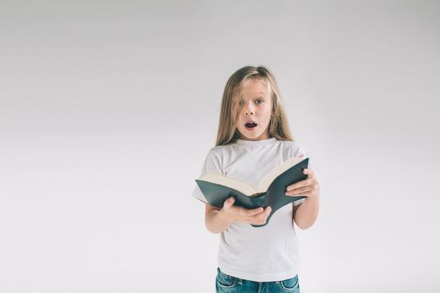 La ragazza in maglietta bianca sta leggendo un libro