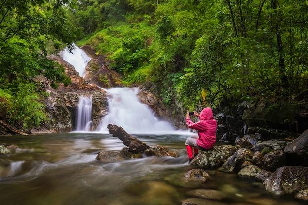 La ragazza in maglione rosso che fa un giro sulla cascata di pi-tu-gro, bella cascata nella provincia di tak, thailand.