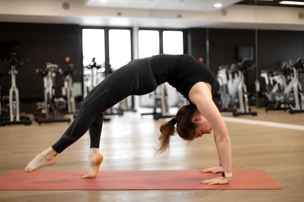 La ragazza in palestra fa yoga per mantenersi in forma o controllare il peso in eccesso.