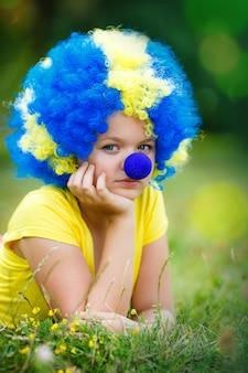 La ragazza in parrucca del pagliaccio con il naso blu sta trovandosi sull'erba verde nel parco