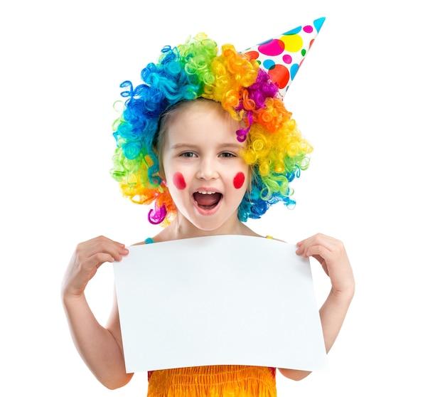 La ragazza in parrucca del pagliaccio tiene la carta in bianco, isolata su fondo bianco