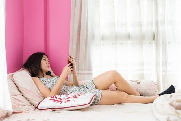 La ragazza in pigiama gioca lo smartphone sul letto