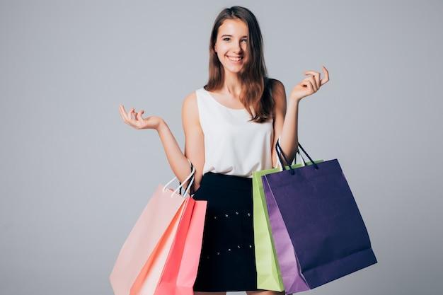 La ragazza in scarpe con i tacchi alti tiene diversi sacchetti di carta della spesa isolati su bianco