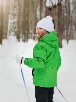 La ragazza in tuta da sci si trasforma in una foresta invernale