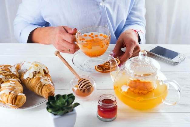 La ragazza in un caffè beve il tè dell'olivello spinoso