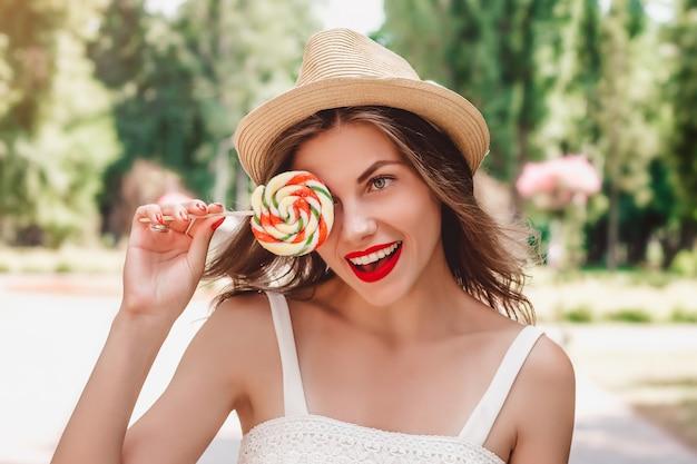 La ragazza in un cappello di paglia e un lecca-lecca colorato multi cammina nel parco