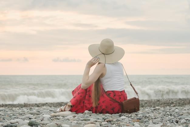 La ragazza in un cappello si siede su una spiaggia di ciottoli. vista posteriore. ora del tramonto