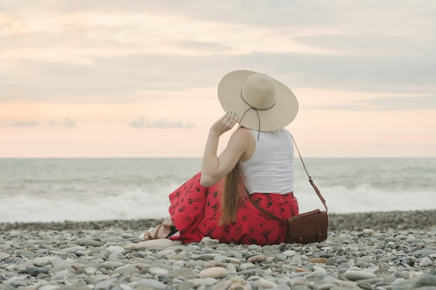 La ragazza in un cappello si siede su una spiaggia di ciottoli.