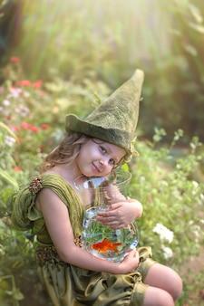 La ragazza in un cappello verde di gnomo abbraccia un acquario con un pesce rosso in un giardino verde.
