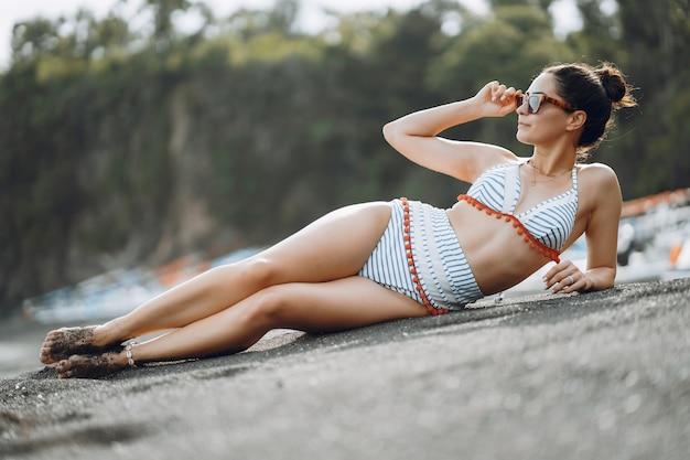 La ragazza in un costume da bagno alla moda ha una spiaggia di riposo