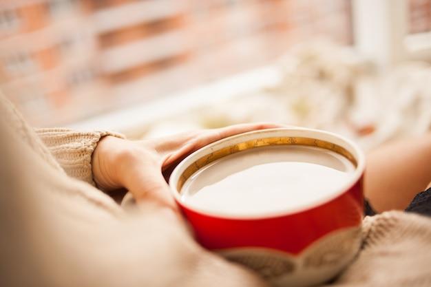 La ragazza in un maglione a maglia accogliente che beve caffè da una tazza rossa