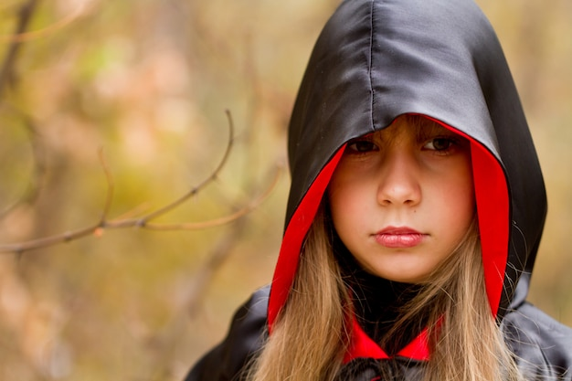 La ragazza in un mantello rosso e nero nella foresta